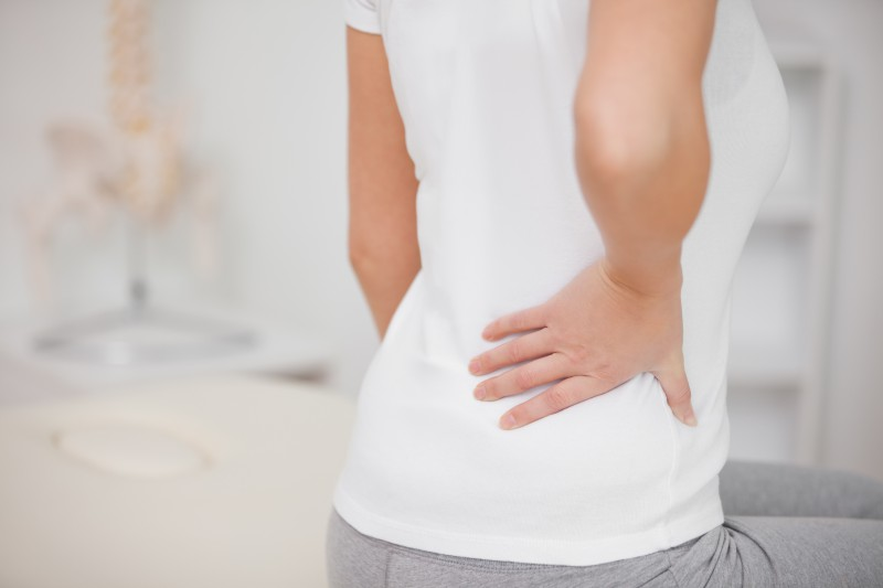 Woman touching her painful back